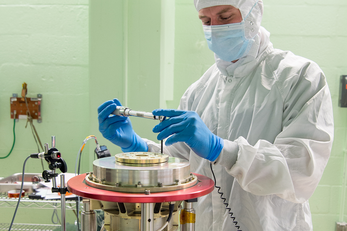 A NASA technician assembles the Half-Angle Mirror (HAM) mechanism
