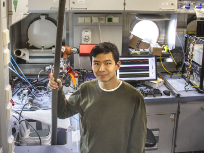 The R/V <em>Falkor</em> contains wet and dry laboratory space, a control room for sonar and ROV operations, and offices. Here, Seaver Wang supplies water to a mass spectrometer in the Wet Lab. Credit: Monika Naranjo Gonzalez (SOI)
