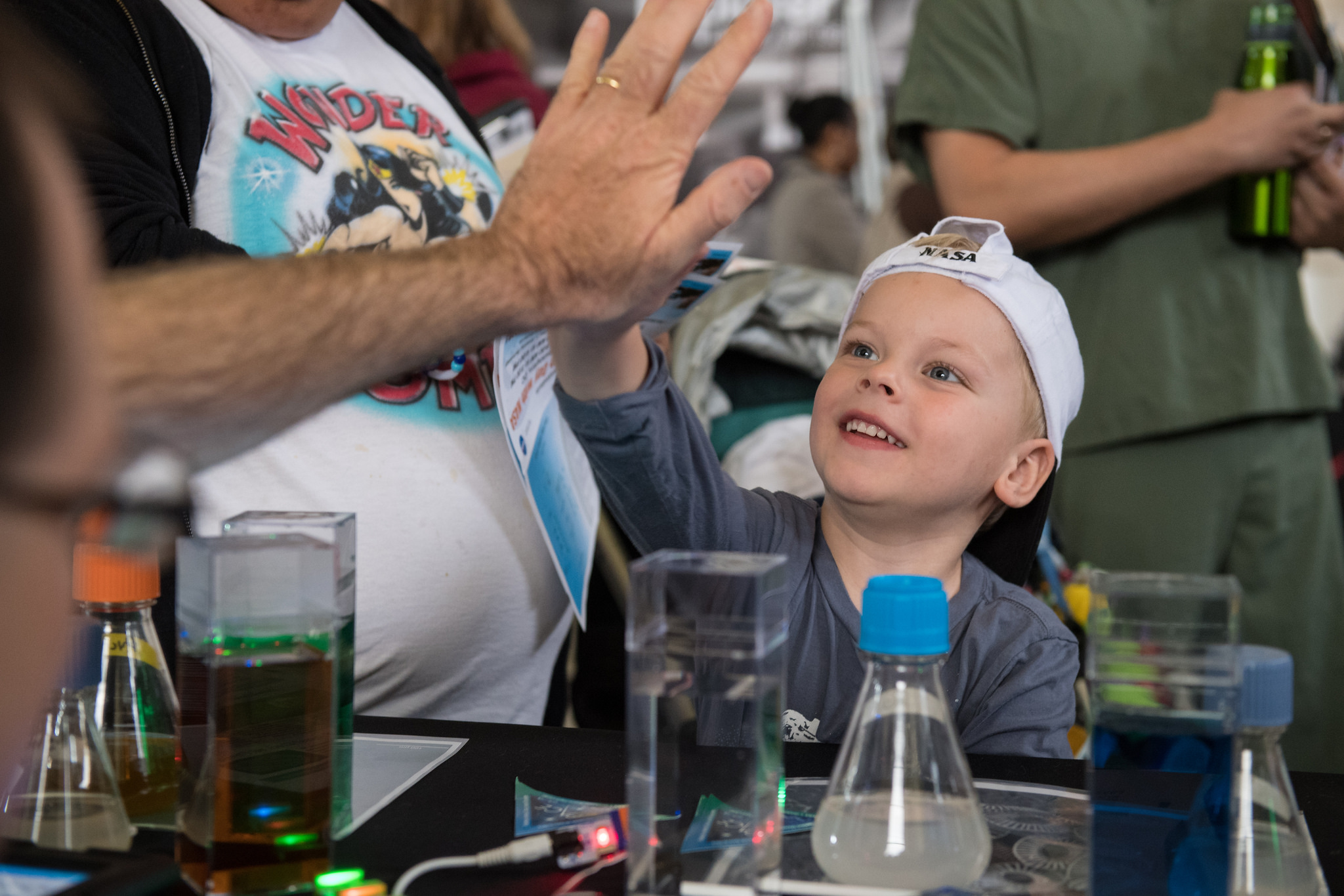 A visitor gives a high five after learning about phytoplankton at the PACE table at the Earth Day event at Union Station in Washington, D.C.