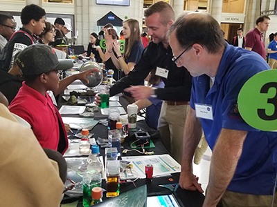 Visitors at the NASA Earth Day Celebration at Union Station (Washington D.C.) check out water with different optical properties while learning about PACE ocean color measurements. Credit: NASA/GSFC