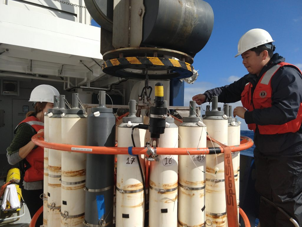 Scientist Yuanheng Xion (University of North Dakota) readies niskin bottles before a test Conductivity, Temperature, and Depth (CTD) cast on a rare cloudless day in the Gulf of Alaska during the EXPORTS cruise.