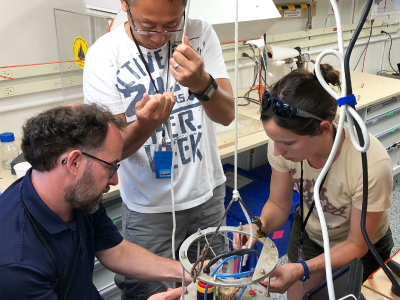EXPORTS scientists prepare a flow cytometer for operation onboard the R/V <em>Sally Ride</em>. Credit: Michael Starobin