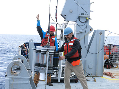 Woods Hole Oceanographic Institution Marine Chemist Ken Buesseler (right) helps deploy a sediment trap from the R/V <em>Roger Revelle</em> during the EXPORTS cruise in the Atlantic. Credit: UCSB/Alyson Santoro