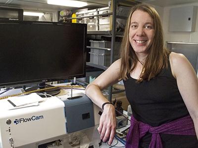 Aimee Neely, Biological Oceanographer, is studying particles using a FlowCam, an instrument that takes pictures of all the particles in the water flowing from a pump in the aft of the R/V <em>Falkor</em>. Credit: Schmidt Ocean Institute/Monica Naranjo Gonzalez