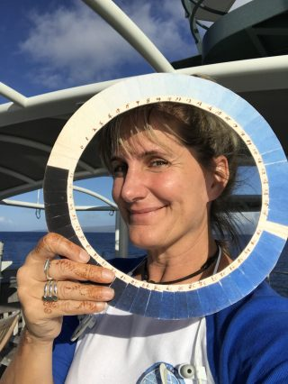 Artist at Sea Kirsten Carlson poses with a replica of a cyanometer, a tool used to measure 'blueness', or the color intensity of blue sky.