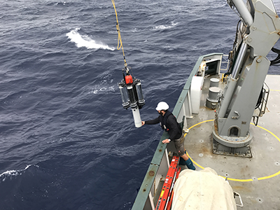 In heavy seas, Philipp Guenther, R/V <em>Falkor</em> Chief Officer, retrieves sediment traps deployed to collect sinking ocean particles 150 meters below the water surface. Credit: NASA/Stephanie Schollaert Uz