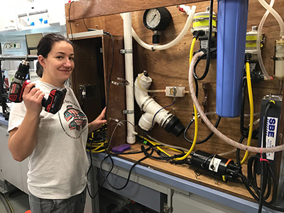 Chief Scientist Ivona Cetinic sets up flow-through on the R/V <em>Falkor</em> for Schmidt Ocean Institute's Sea to Space Particle Investigation. Credit: Schmidt Ocean Institute