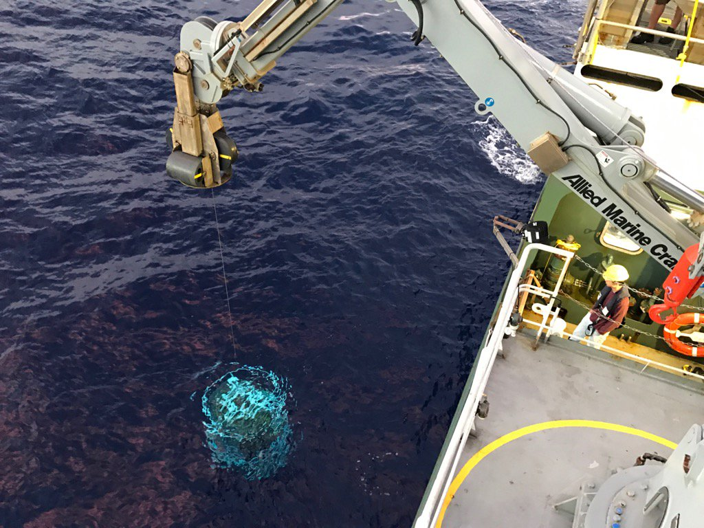 A Conductivity, Temperature and Depth (CTD) sensor is lowered off the side of the R/V <em>Falkor</em> at sunrise.