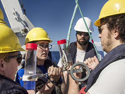 Melissa Omand, Colleen Durkin, Phillipp Guenther and Ben Knorlein make sure that the sediment trap is ready and steady as they prepare to deploy it off the R/V <em> Falkor's</em> aft deck. Credit: Schmidt Ocean Institute