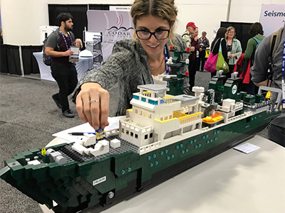 Carlie Wiener of the Schmidt Ocean Institute with a LEGO model of the R/V <em>Falkor</em>, the research vessel used for the Sea to Space Particle Investigation. Credit: Schmidt Ocean Institute