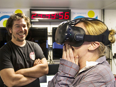 Ben Knorlein, Computer Scientist, observes Melissa Omand as she reacts to the first Virtual Reality experience created on board Falkor from holographic images of plankton suspended in the water. Credit: Schmidt Ocean Institute