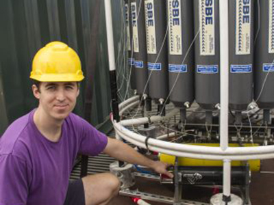Noah Walcutt examines the holographic camera installed in the CTD rosette. The camera is able to capture around 40,000 images in a single CTD cast. Credit: Schmidt Ocean Institute
